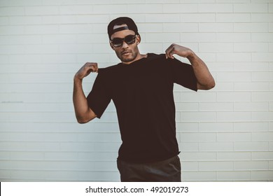 Feeling just casual. Handsome young African man touching his T-Shirt and looking at camera while standing in front of the brick wall outdoors