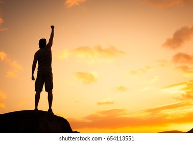 Feeling like a winner! Silhouette of man pumping his fist in the air. Get out get fit concept.
