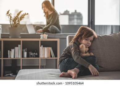 Feeling lonely. Full length portrait of small sad kid left alone on sofa with teddy bear in hand at home. Her mom on the background ignoring her while browsing the net