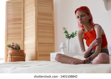 Feeling miserable. Red-haired anorexic woman with tattoos on arms feeling miserable while sitting on bed