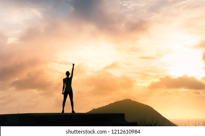 Feeling motivate- winning- strong. Young woman standing on mountain top with fist in air.