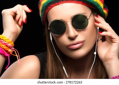 Feeling the Music. Close up Fashionable Young Woman, Wearing Rastafarian Hat, Trendy Round Sunglasses and Colorful Bracelets, Enjoying Party Music Through Headphone. Portrait Isolated on Black.