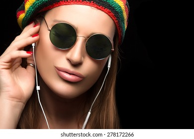 Feeling the Music. Close up Fashionable Young Woman, Wearing Rastafarian Hat and Trendy Round Sunglasses, Enjoying Party Music Through Headphone. Portrait Isolated on Black with Copy Space for Text.