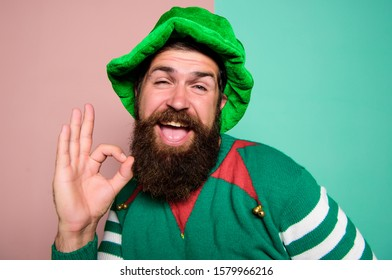feeling ok. happy celebration. cheerful man with beard have fun. ireland beer tradition. Winter carnival. irish pub party. st patricks day. happy bearded hipster in green hat. christmas elf.
