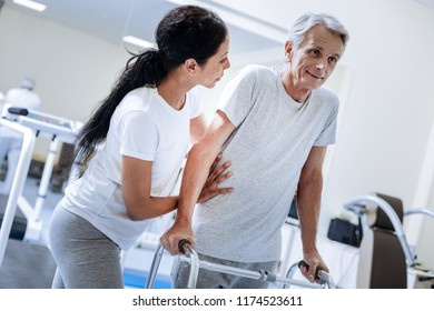 Feeling optimistic. Aged ill man feeling optimistic about his recovering while leaning on a walking frame with a kind attentive qualified doctor helping him to walk