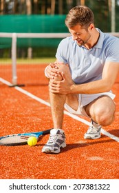 Feeling pain in knee. Close-up of tennis player touching his knee and grimacing while sitting on the tennis court
