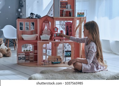 Feeling playful. Cute little girl playing with a dollhouse while sitting on the floor in bedroom