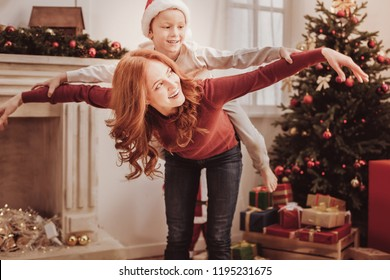 Feeling playful. Positive little child riding on mothers back while holding her hands