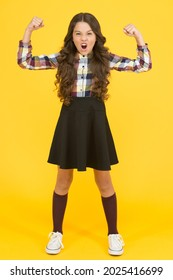 Feeling power of being a girl. Strong girl yellow background. Little girl show strength flexing arms. School look of fashion girl in uniform. Health and strength. Back to school fashion. Formal style