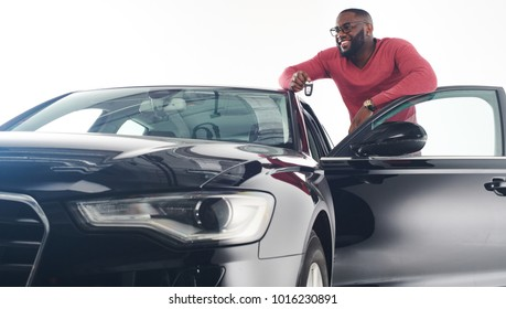 Feeling proud. Attractive young african man in stylish outfit standing near black luxury car model 2018 car and leaning on its roof.