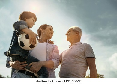 Feeling proud. Exuberant smiling loving daddy son and grandfather looking at each other while the dad holing his son in his hands and the son holding his ball
