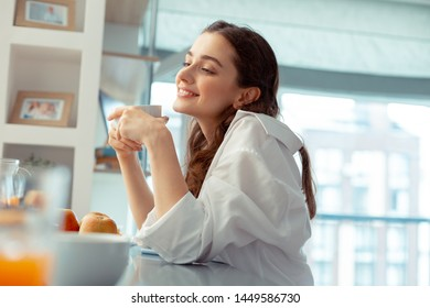 Feeling relaxed. Beautiful young woman wearing white shirt feeling relaxed drinking coffee