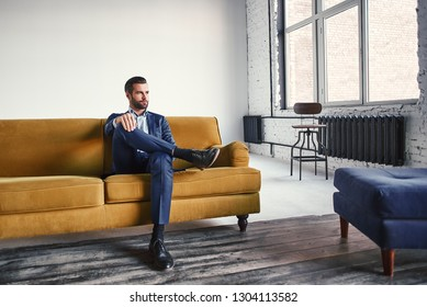 Feeling relaxed...Handsome and stylish young businessman is resting on sofa and thinking about business ideas