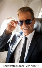 Feeling safe and comfortable. Cheerful mature businessman sitting at his seat in airplane and adjusting his sunglasses