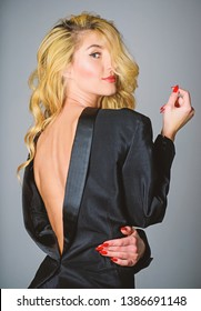 Feeling so sexy in masculine clothes. Tempting horny sexy woman enjoy wearing oversize jacket. Fashion concept. His jacket suits me. Girl playful sexy blonde wearing male jacket on naked body.