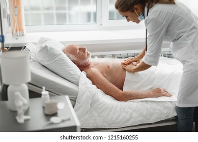 I am feeling sick. Side view portrait of shirtless old man lying in bed during medical examination
