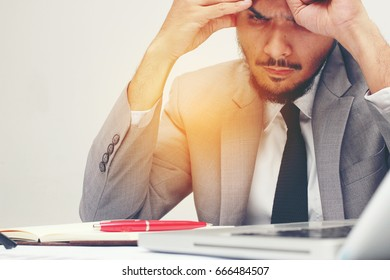 Feeling sick and tired from working. Frustrated young man are stressed while sitting at his working place in office, business, people, paperwork and deadline concept
