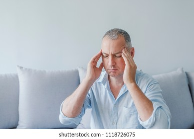 Feeling stressed. Frustrated handsome young man touching his head and keeping eyes closed while sitting on the couch at home. Stress and overwork concept