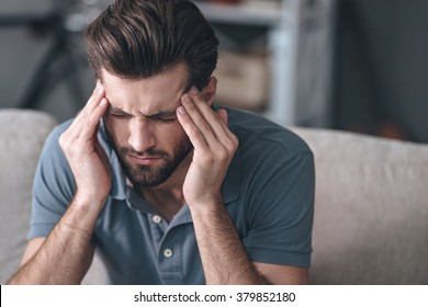 Feeling stressed. Frustrated handsome young man touching his head and keeping eyes closed while sitting on the couch at home