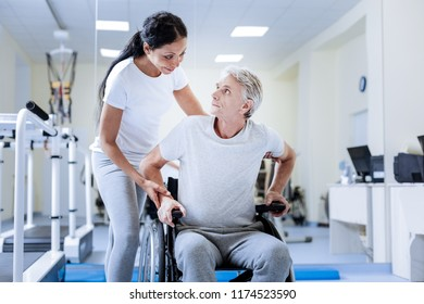Feeling support. Aged emotional disabled man sitting in a wheelchair and feeling worried while being in a special rehabilitation center and looking at his kind attentive qualified doctor
