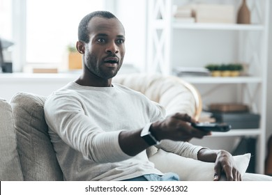 Feeling surprised. Handsome young African man holding a remote control while sitting on the sofa at home
