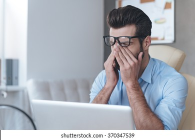 Feeling tired. Frustrated young handsome man looking exhausted and covering his face with hands while sitting at his working place