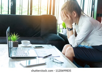 Feeling tired and stressed young woman of working age is working on table.