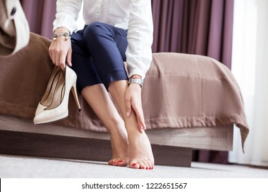 Feeling of tiredness. Beautiful nice woman touching her legs after walking on high heels