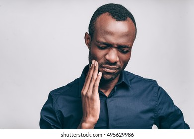 Feeling toothache. Frustrated young African man touching his cheek and keeping eyes closed while standing against grey background