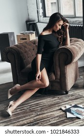 Feeling upset. Frustrated young woman in elegant black dress touching her head with hand while sitting in the armchair