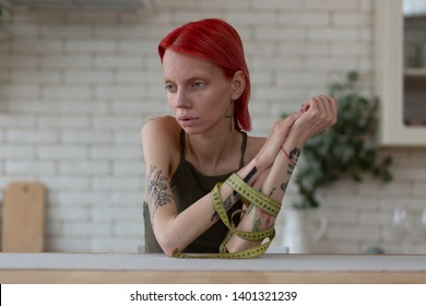 Feeling vulnerable. Red-haired anorexic woman feeling vulnerable suffering from eating disorder