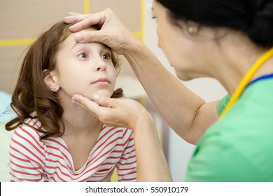 Feeling weak. Senior female pediatrician with a beautiful young girl for a patient doctor examining eyes of a cute young girl checkup doctor pediatrics professional hospital weakness sickness