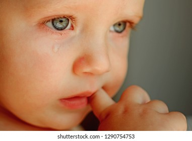 Feeling weepy. Baby with tear rolling down his cheek. Little boy child with sad face. Little baby crying. He is a cry baby.