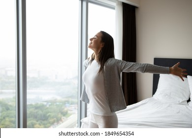 Feeling wings behind back. Happy carefree young female tourist traveler client visitor of luxury hotel standing in suite room spreading arms to sides admiring beautiful sight from panoramic window