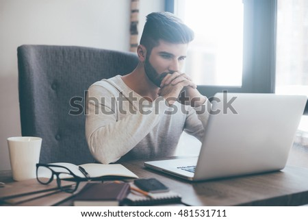 Feeling worried about new project. Thoughtful young man holding hands on chin and looking at the laptop while sitting at his working place in office