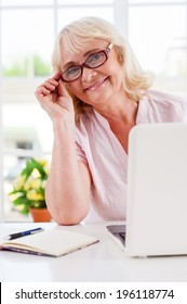 Feeling young and active. Cheerful senior woman adjusting her glasses and smiling while working on laptop