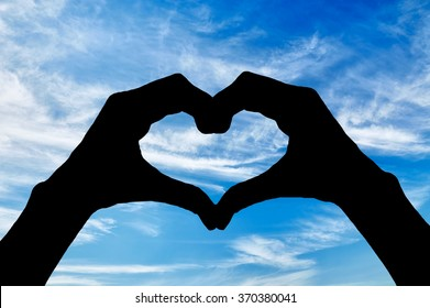 ?oncept of feelings and emotions. Silhouette of the heart hand gesture against a blue sky