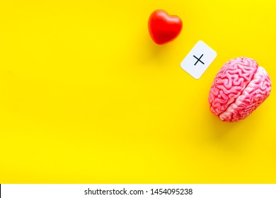 feelings and mind concept with brain plus heart on yellow background top view mock up