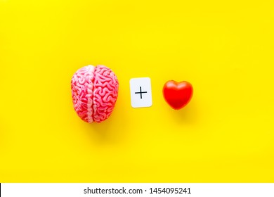 feelings and mind concept with brain plus heart on yellow background top view