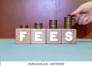 Fees Hidden Service Business concept. Hand puts coin on growing coins pyramid on wooden blocks with fees word. Cost, fee and taxes.