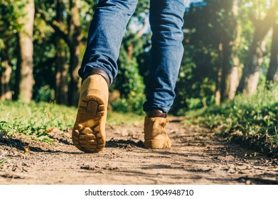 feet of an adult wearing boots to travel walking in a green forest. travel and hiking concept.