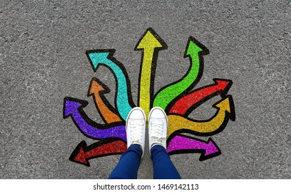 Feet and arrows on road background. Pair of foot standing on tarmac road with colorful graffiti arrow sign choices, creative and idea concept. Selfie woman wearing white shoe or sneaker. Top view.