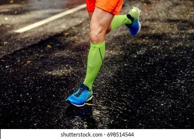 feet athlete man in compression socks running black road asphalt