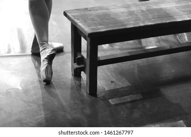 The feet of a ballerina in pointe standing in a rehearsal room near a wooden bench