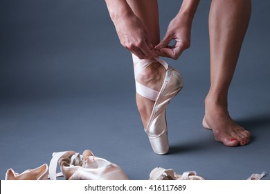 Feet of ballerina tying pointe shoes