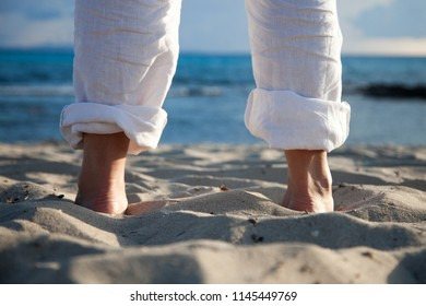 Feet of a barefoot man in the sand of a beach at dawn seen from behind