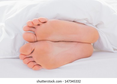 Feet in a bed under the duvet