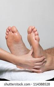 Feet being massaged by female masseuse on white towel
