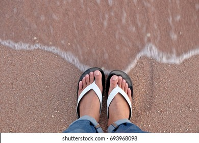 Feet in black and white slipper on the beach with motion wave. Focus on feet.