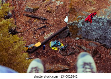 feet in boots hang from a high cliff overlooking the autumn forest. First-person view